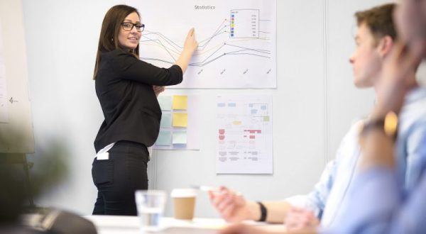 Young female professional explaining graph to male executives in office
